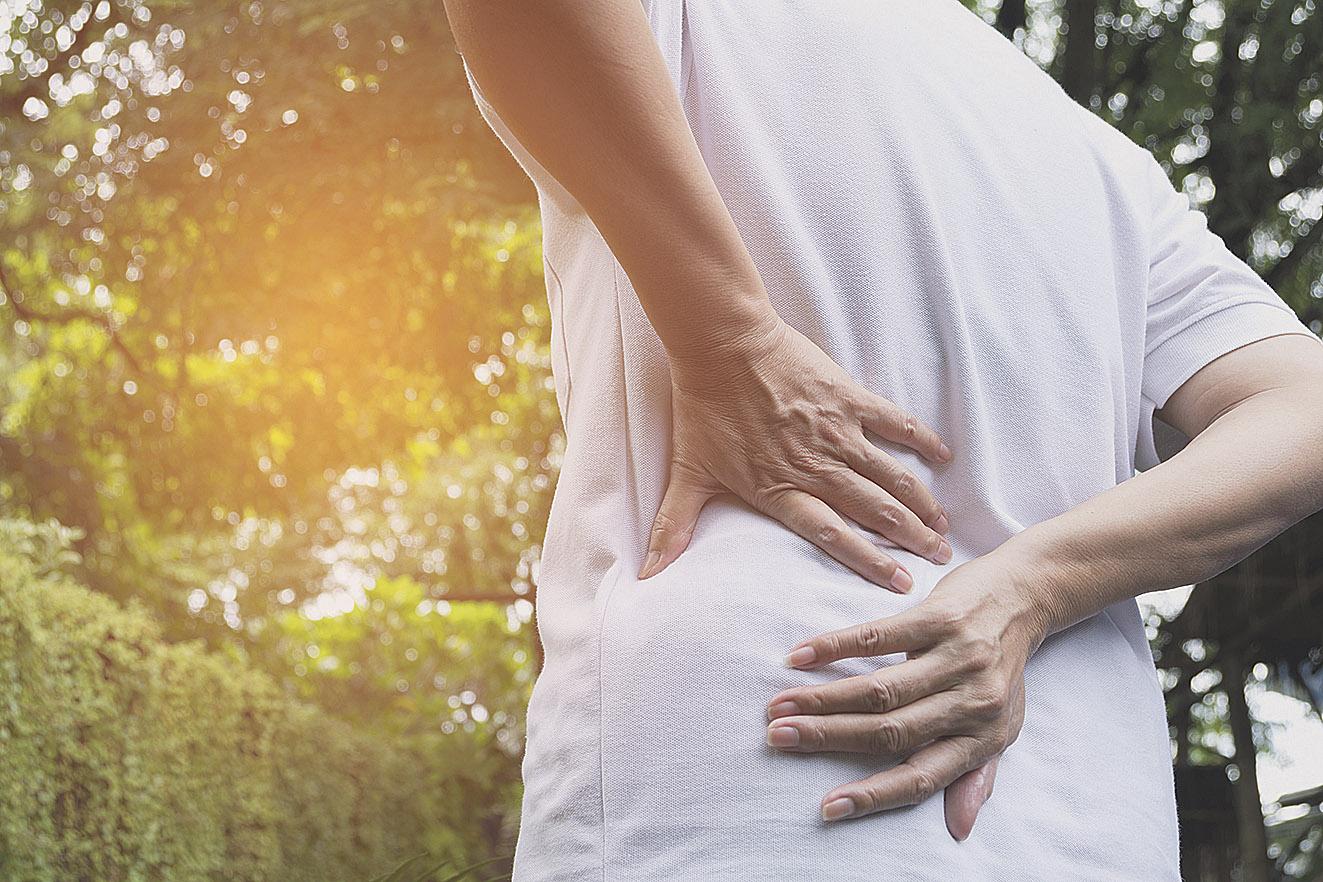 Sportler greift sich an die Hüfte. Thema: Rückenschmerzen