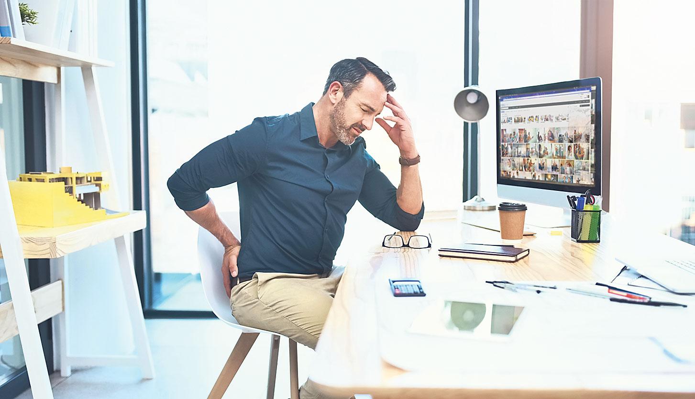Ein Mann, der mit schmerzverzogenen Gesicht am Schreibtisch sitzt.