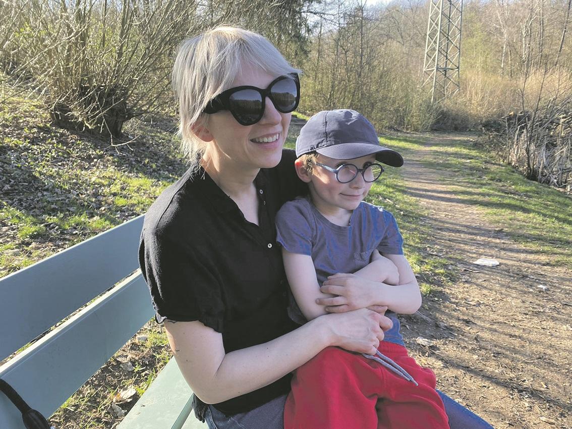 Jenny Ludwig und ihr Sohn, auf einer Bank im Wald.