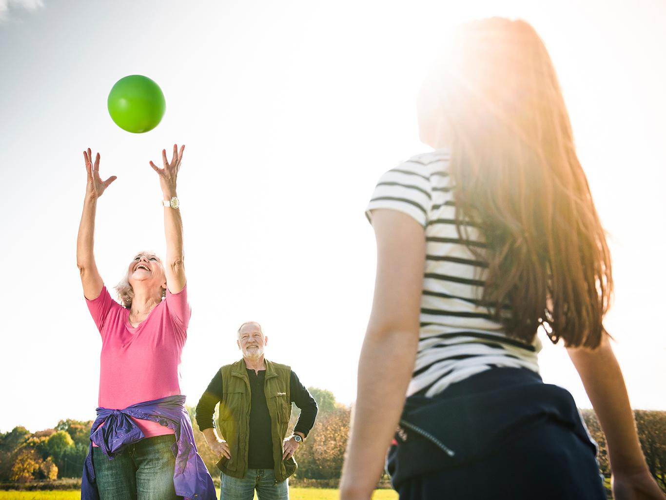 Seniorenpaar spielt mit jungem Mädchen Ball auf einer Wiese.