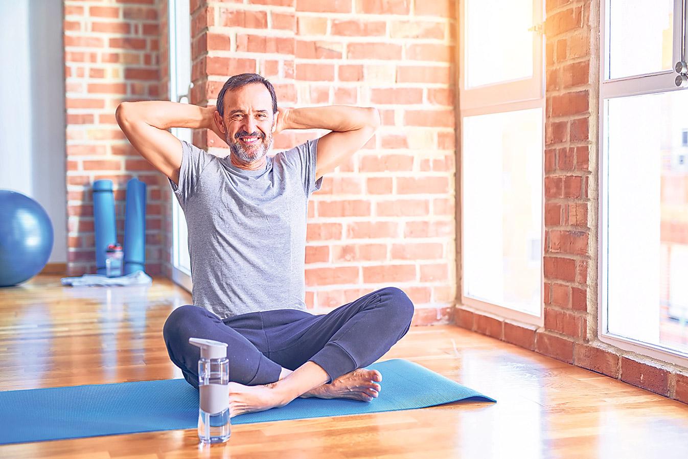 Mann sitzt auf Yogamatte und streckt sich.