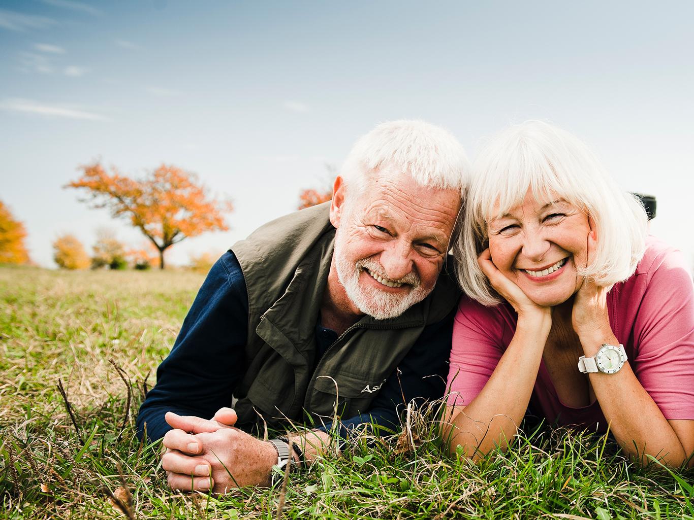 Seniorenpaar liegt auf Wiese
