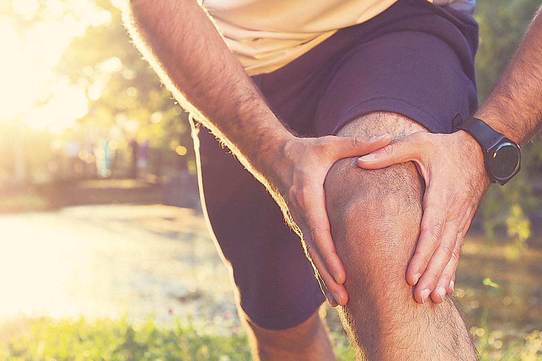 Detailansicht: Jogger fässt sich an sein Knie.