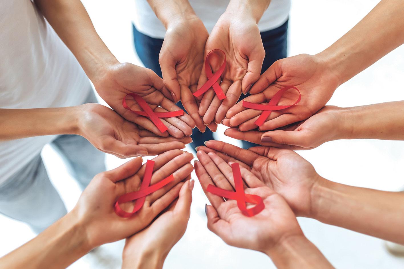 Fünf Händepaare mit jeweils einer roten Schleife auf der Handfläche.