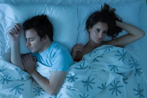 Ein Mann und eine Frau neben einander liegend im Bett. Der Mann schläft, während die Frau wach daneben liegt.