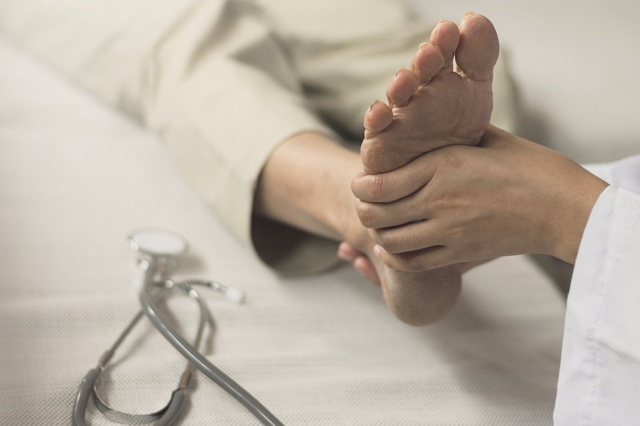 Mediziner untersucht den Fuß einer Seniorin. Thema: Diabetisches Fußsyndrom