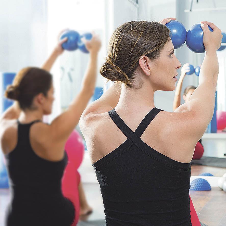 Zwei Frauen führen Rückenübungen aus. Thema: Chronische Rückenschmerzen
