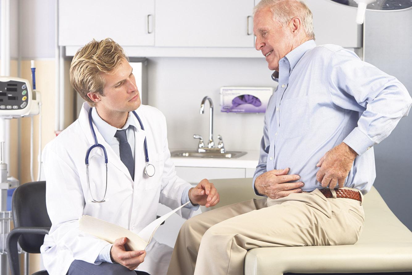 Älterer Patient sitzt bei seinem Arzt und zeigt auf seine Hüfte. Thema: Metallallergie bei künstlichen Gelenken oder Implantaten