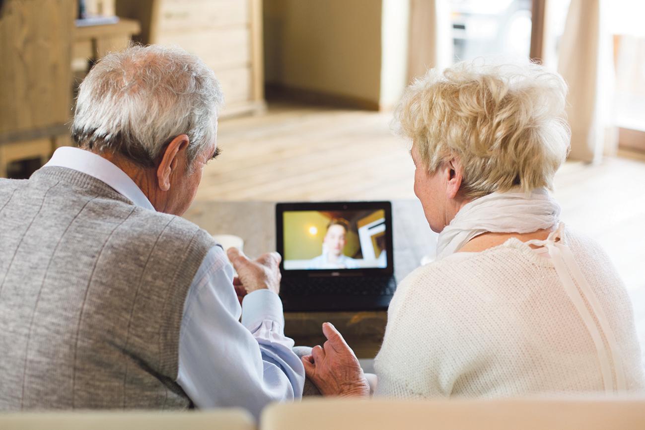 Ein älteres Paar spricht mit dem Sohn per Videotelefonie.