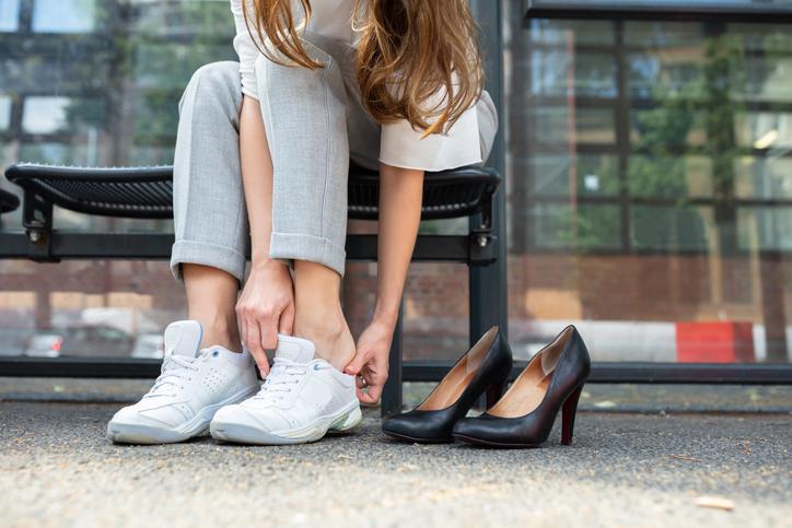 Eine Frau wechselt von High Heels zu bequemen Sneakern.