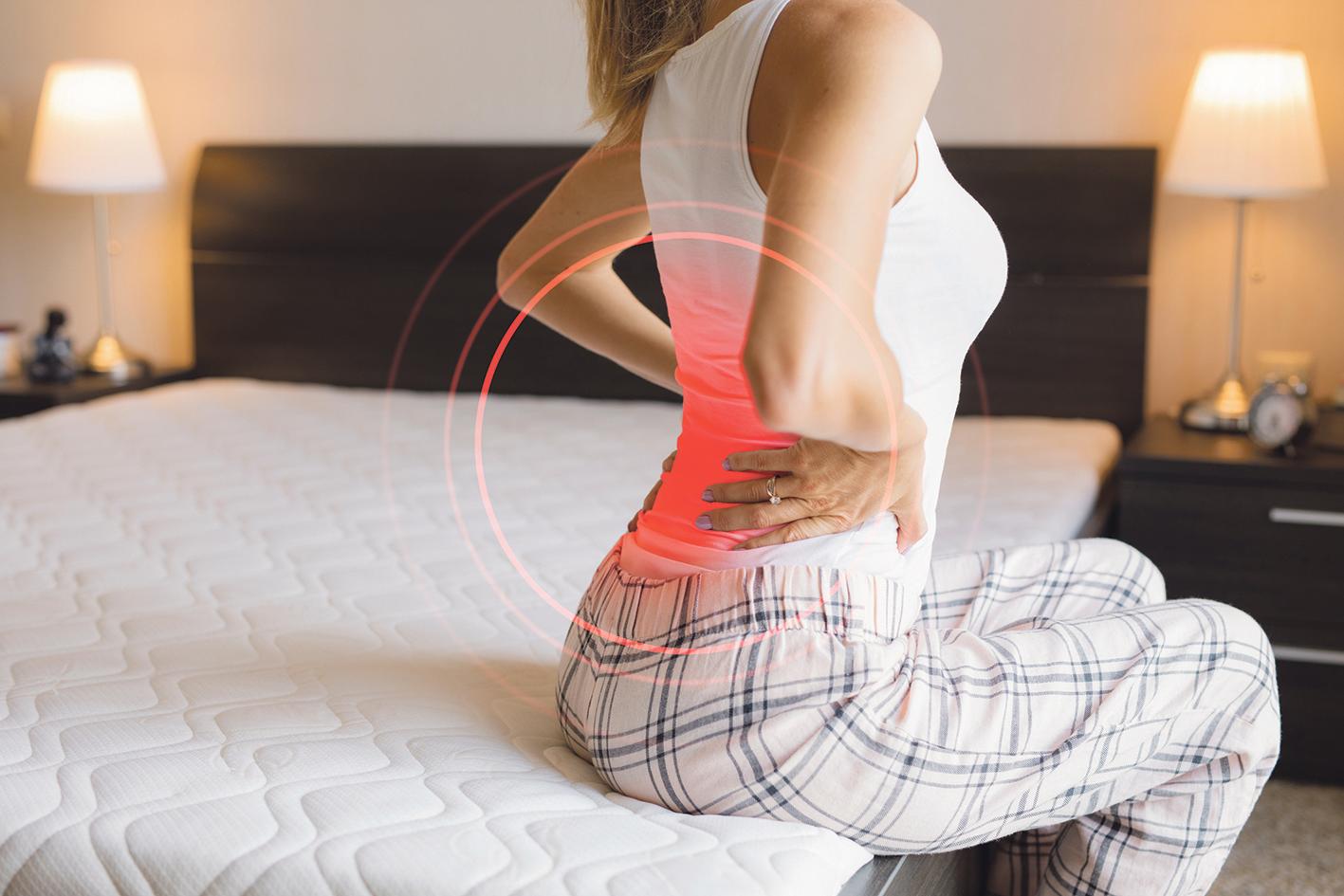 Frau sitzt aufrecht auf dem Bett und hat Schmerzen im unteren Rücken.