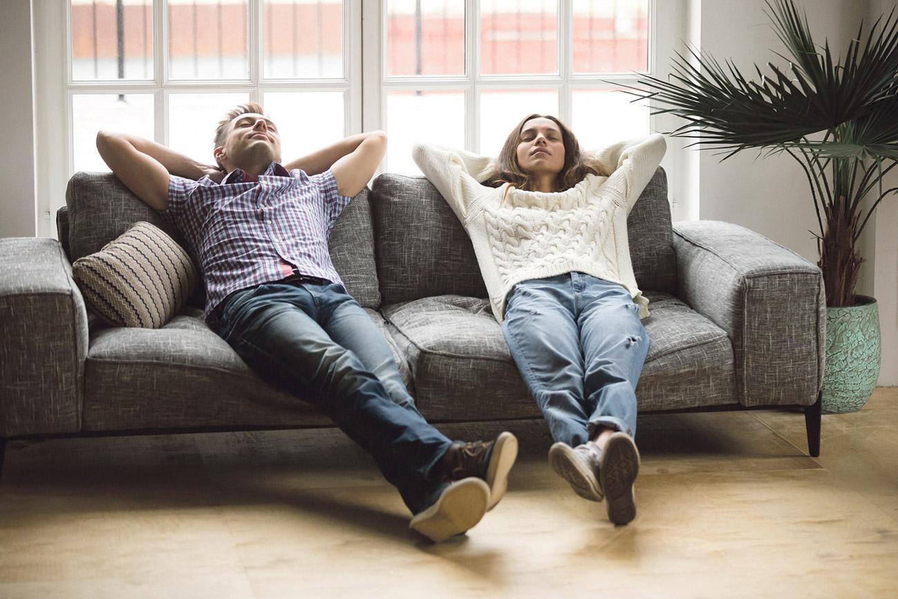 Paar, was auf der Couch liegt und entspannt.