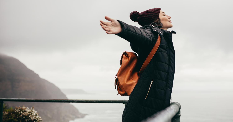 Eine Frau steht an einer Küste und atmet tief ein.