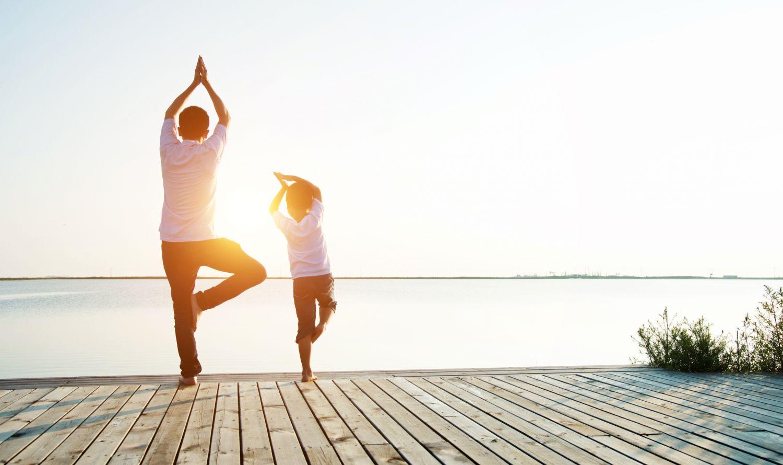 Vater und Kind machen Yoga am See.
