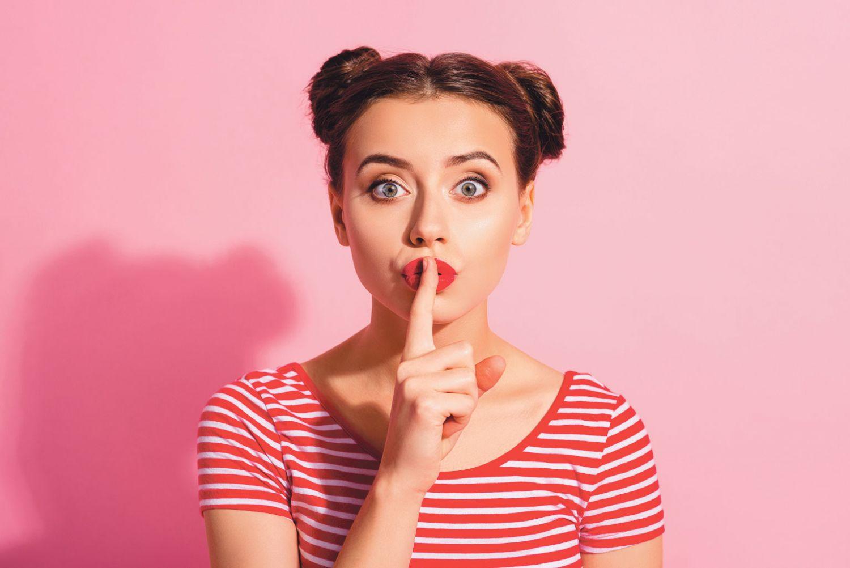 Frau, die ihren Zeigefinger vor den Mund hält.