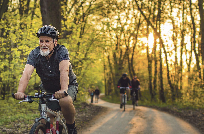 Senior fährt mit dem Rad durch den Wald. Thema: Alterungsprozess