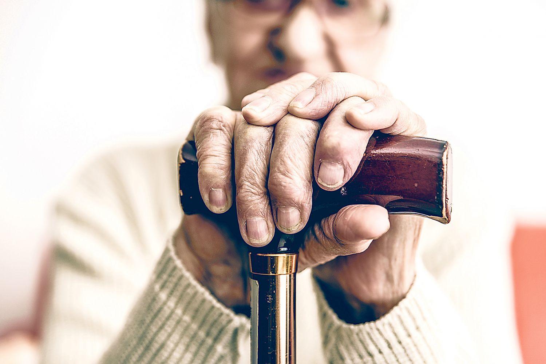 Detailaufnahme Hand: Alter Mann stützt sich auf Gehstock