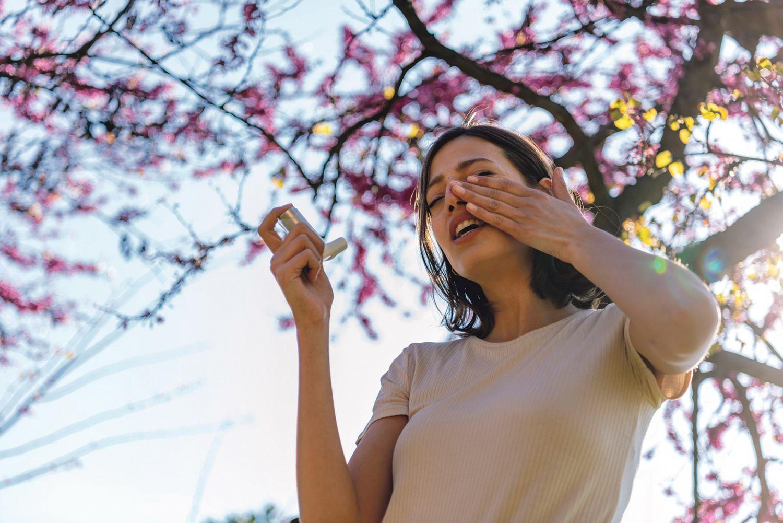 Eine Frau mit Inhalator unter einem blühenden Baum