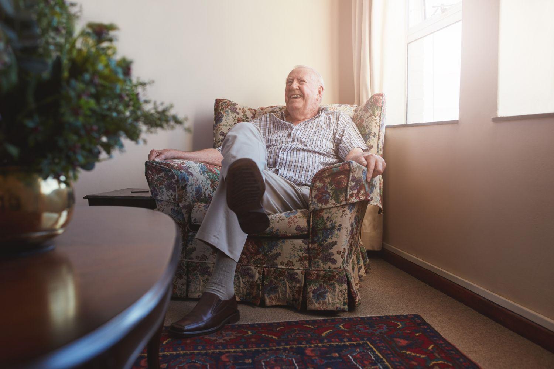 Lachender Senior in seinem Sessel