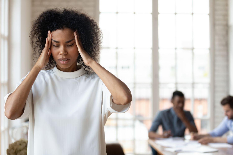 Frau hält sich den Kopf vor Schmerzen