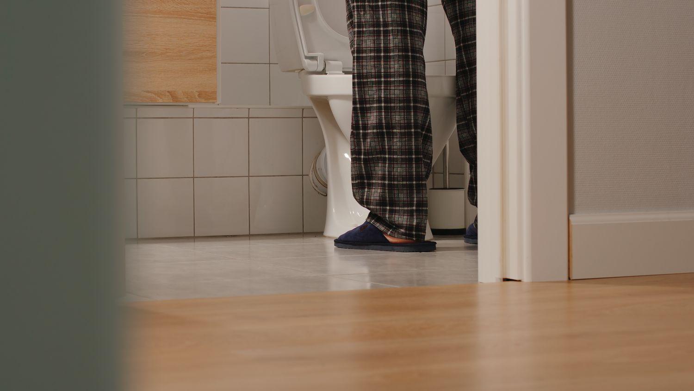 Ein Mann steht vor einer Toilette.