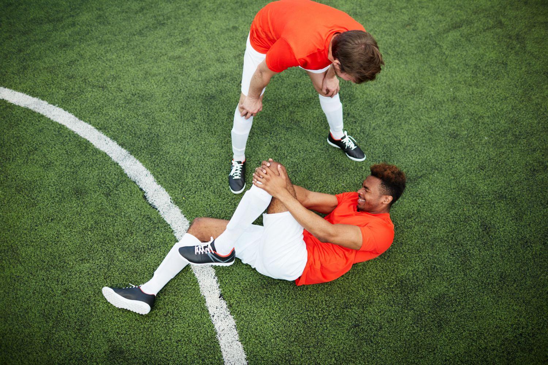 Fußballer liegt auf dem Boden und hält sich sein verletztes Knie