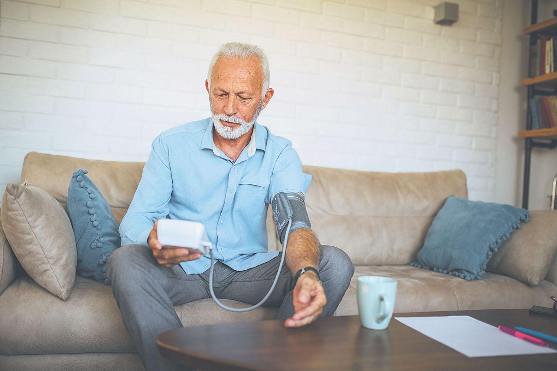 Ein älterer Mann mit einem Blutdruckmessgerät.