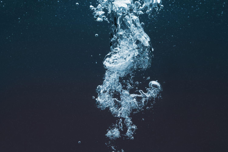 Luftbläschen steigen im Wasser nach oben