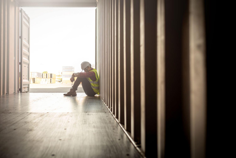 Ein erschöpfter Bauarbeiter sitzt an eine Wand gelehnt. Thema: Alltag mit COPD