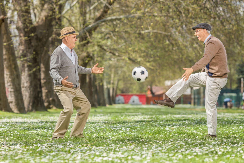 Zwei Senioren spielen Fußball im Park. Thema: Bewegungsmangel