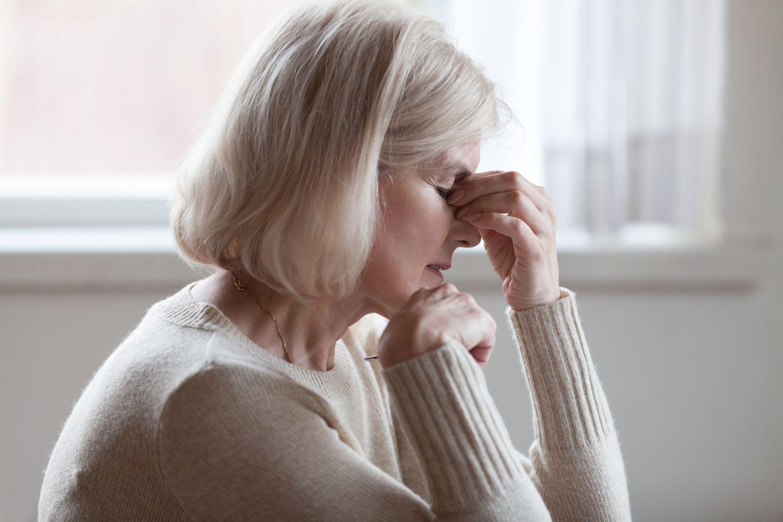 Ältere Frau, die sich an den Kopf fässt wegen Schwindelgefühl.