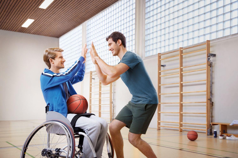 Zwei junge Männer, die sich beim Basketball abklatschen. Einer von ihnen sitzt im Rollstuhl.