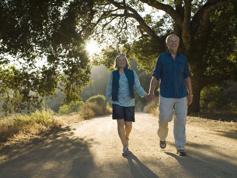 Älteres Pärchen (Best Ager) geht Hand in Hand spazieren.