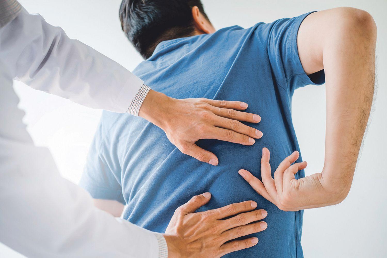 Ein Mann lässt seinen Rücken beim Arzt untersuchen.