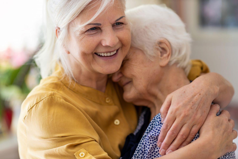 Zwei ältere Frauen, die sich umarmen.
