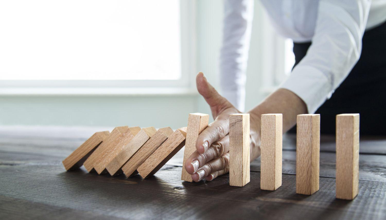 Eine Frau stoppt mit der Hand eine Reihe umfallender Dominosteine.