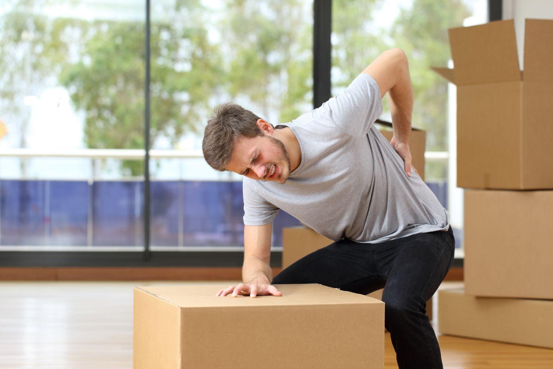 Mann sitzt auf einem Umzugskarton und fässt sich an den Rücken vor Schmerz.