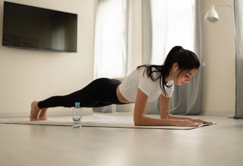 Eine junge Frau macht zuhause Gymnastik.