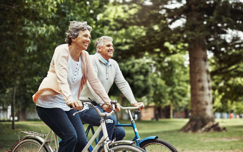 Älteres Pärchen ist mit Fahrrädern unterwegs.