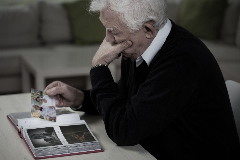 Senior schaut sich ein Foto-Album an.