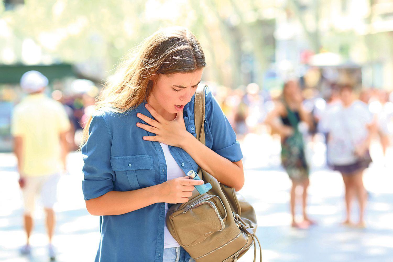 Eine Frau hält sich die Hand an die Brust. Thema: Emphysem der Lunge