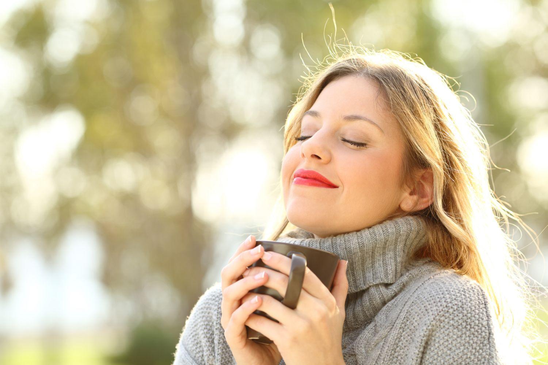 Eine Frau atmet tief ein und hält eine Tasse vor sich.