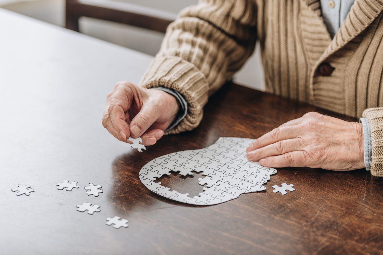 Ein Mann ist mit einem Puzzle in Form eines Kopfes beschäftigt. Thema: Demenzprävention