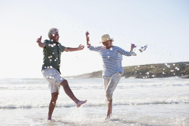 Älteres Paar, lachend und tanzend am Strand.