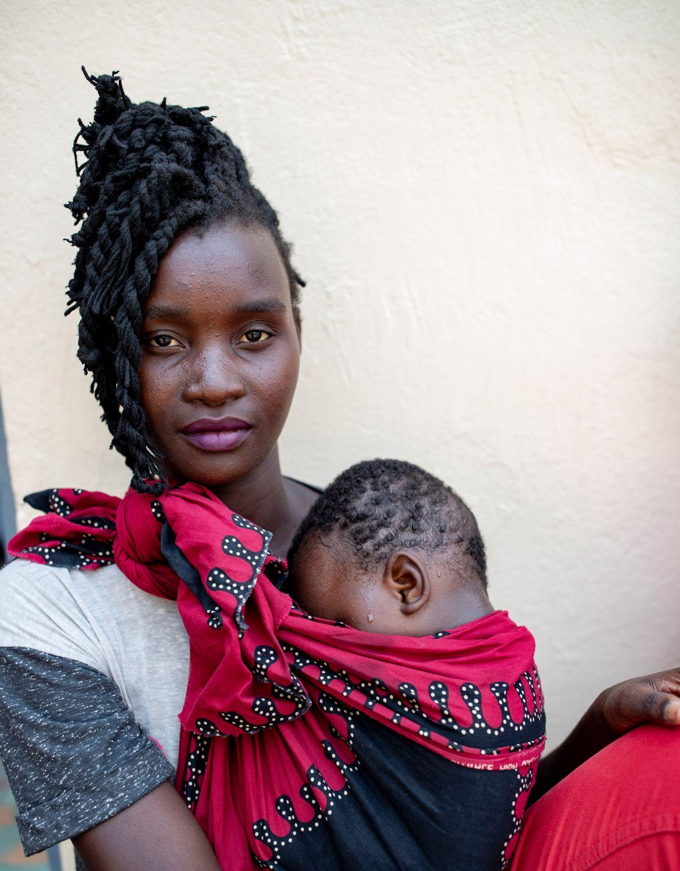 Eine junge Mutter mit ihrem Baby in einem Tuch.