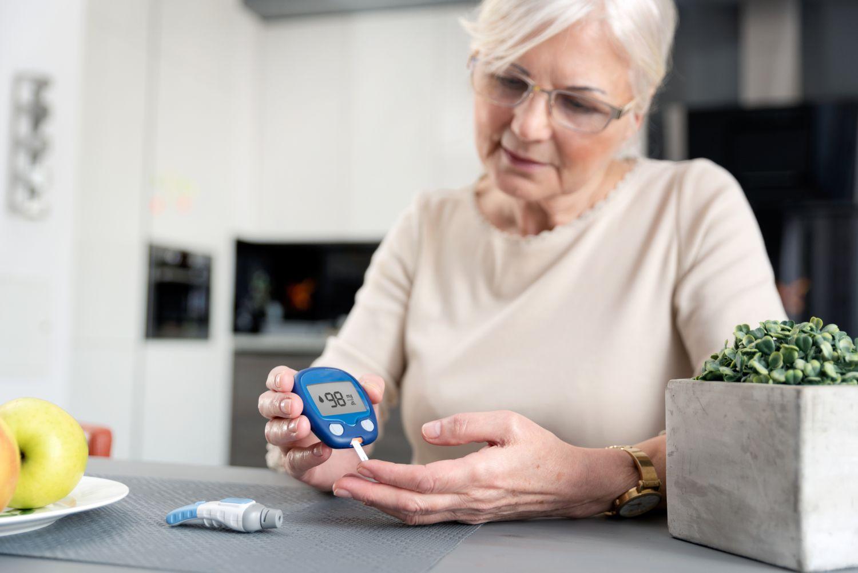 Seniorin überprüft ihren Blutzuckerspiegel