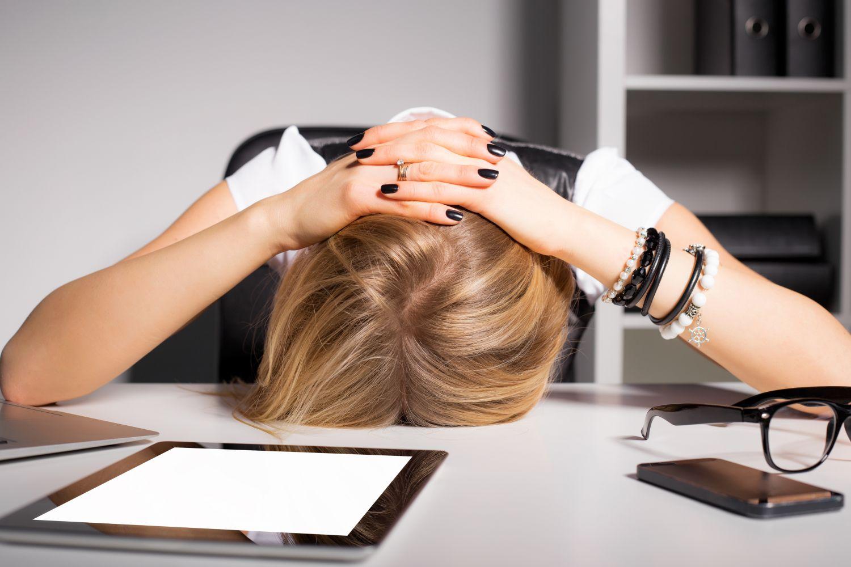 Eine Frau liegt vornüber gebeugt auf dem Schreibtisch aufgrund von starken Kopfschmerzen.