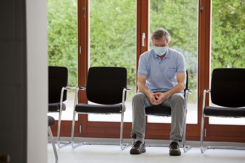 Mann mit Atemschutzmaske sitzt in einem Wartesaal.